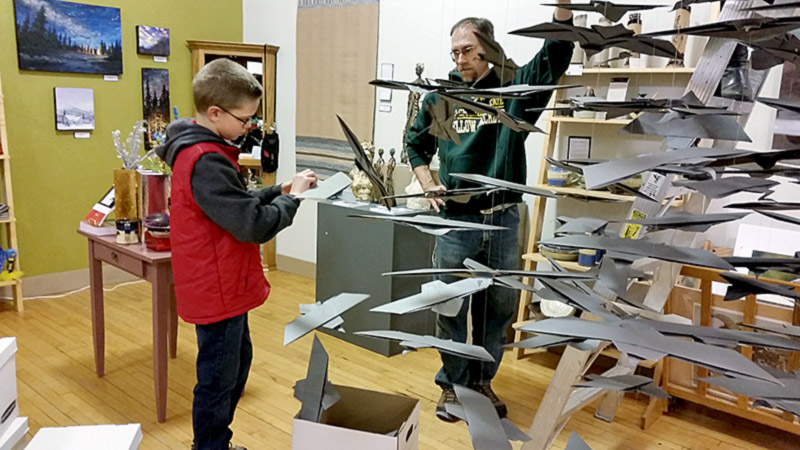 Justin adjusted each falcon beak before it was hoisted up!  Dad looks on.