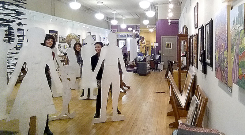 The Matthews' staff posing with the blank flat people--created by Ava Sauter.